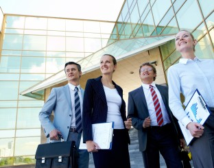 Group of confident employees with documents looking aside outdoo