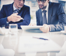 Image of two young businessmen discussing document in touchpad a