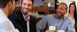 Happy young businessmen drinking beer and talking at pub after w