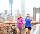 Running couple. Runners jogging outside in rain. Asian woman and