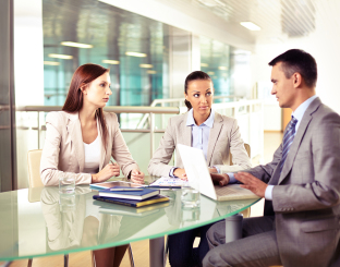Group of three business partners interacting at meeting in offic