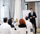 young  male business man giving a presentation at a  meeting sem