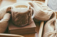 Cup of hot tea with lemon dressed in knitted warm winter scarf o