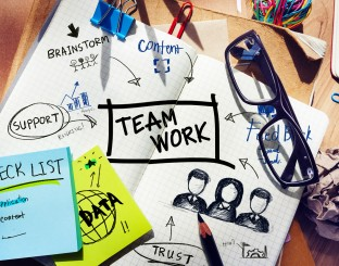 Desk with Tools and a Notebook with Ideas About Teamwork