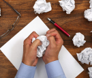 Crumpled paper and businessman tearing up another paper ball for