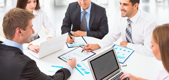 Young business people sitting at desk, using computer at busines