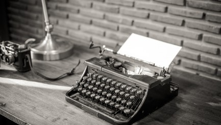 Black And White Of An Old Typewriter With Paper On A Wooden Tabl